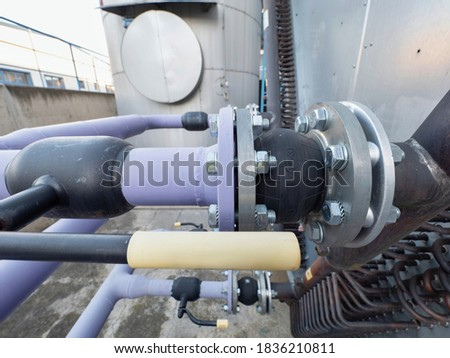 Flanges and ball valves with vibration rubbery damper on connection of air to air industry cooler. Air vent pipe of air conditioning system chiller outside  Stockfoto ©