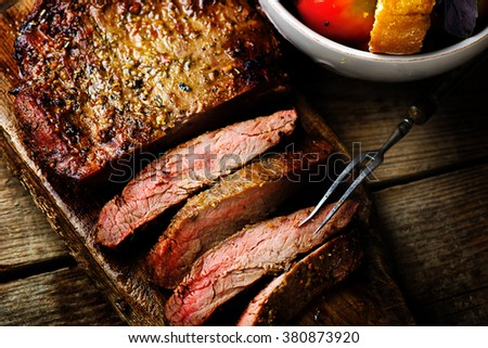 flank steak  with tomato salad and glass of beer. style vintage.  selective focus.top view