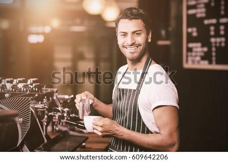 flare against portrait of handsome waiter adding milk to coffee