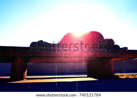 Flare, soft focus. Silhouette in sunbath. Drank adult man rests on stony  bench in park, Sharp sun rays make contours around sleeping body.  #740121784