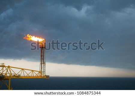 Flare stack and flare bridge while burning toxic gas and release over pressure of production process in sunset time. #1084875344