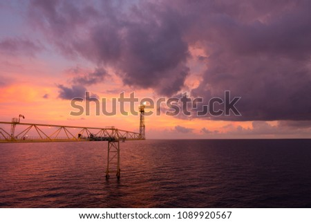 Flare stack and flare bridge while burning toxic gas and release over pressure of production process in sunset time. #1089920567
