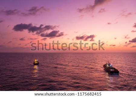 Flare stack and flare bridge while burning toxic gas and release over pressure of production process in sunset time with supply boat for industrial concept. #1175682415