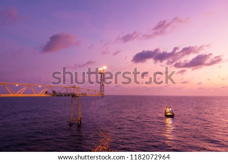 Flare stack and flare bridge while burning toxic gas and release over pressure of production process in sunset time with supply boat for industrial concept. #1182072964
