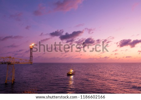 Flare stack and flare bridge while burning toxic gas and release over pressure of production process in sunset time with supply boat for industrial concept. #1186602166