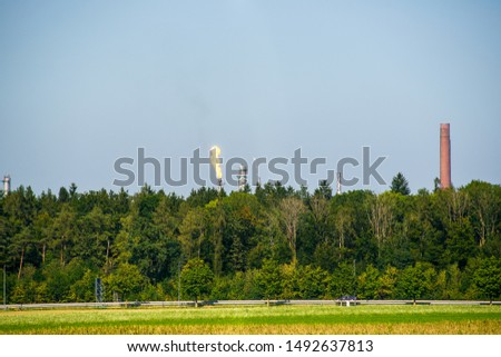 Flare stack behind a forest at a refinery. #1492637813