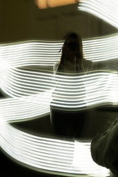 Flash drawing technique with timelapse. Students are practicing the flash drawing technique in a photograhy class. You can see a woman practicing the technique with a flow of light surrounded her body