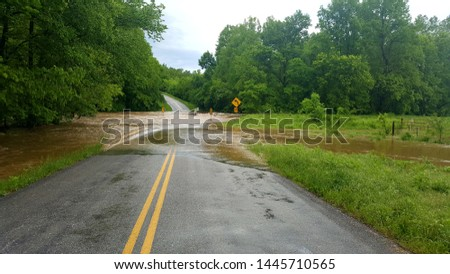 Flash flood water rushes over a low-water bridge on a rural highway near Long Lane, Missouri. Stock photo ©