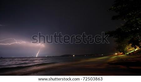 Flash in dark night sky over sea and yellow coast