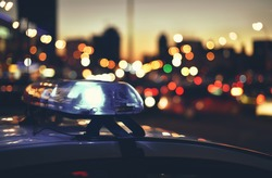 flashers of police car on background night city traffic
