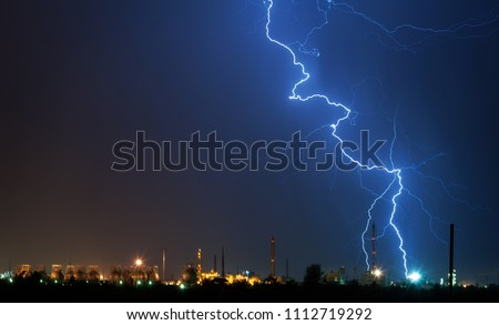 Flashes of lightning in the night sky. Lightning strike. Lightning near the factory. Night sky. Storm cloud. A flash of lightning. Industrial landscape before the storm