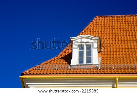 Flashing orange tiled roof on blue sky and one garrret window in Riga old town, Latvia