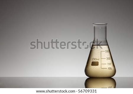 flask with yellow liquid to the light and white background - stock photo