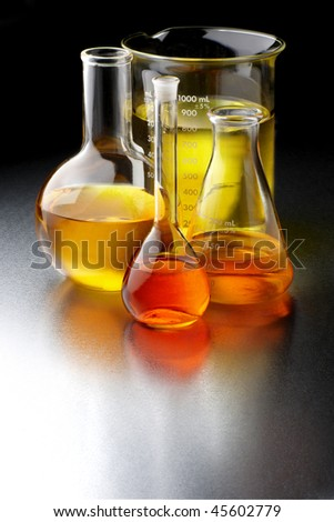 Flasks and beakers filled with bio fuels, shot on textured metal lab table with space for copy