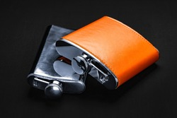 Flasks for alcohol on the table. Steel flask with leather trim on a black background. Tanks for whiskey, rum, vodka and various alcohol. Lifestyle and travel.