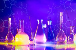 Flasks of different shapes and volumes on a lilac background. Chemical concept. Development of new food additives. Evaporation of substances. Study of chemistry.