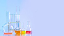 Flasks with multi-colored reagents. Flasks of different sizes in a chemical laboratory. Reagents experiments. Place for text. Elements for the manufacture of medicines. Concept - sale of chemicals