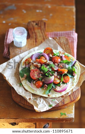 Flat bread with Cherry Tomatoes, Bacon and Chard on a wooden board - stock photo