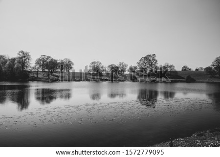 Flat calm country park lake. Reflections of trees make a calming picture.