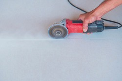 Flat ceiling cutter with an electric cutter. Flat ceiling cutter with an electric cutter. worker cutting ceiling with an angle grinder in the construction site.