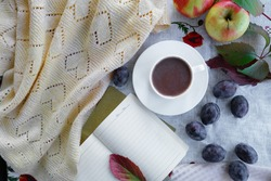 Flat composition with a cup of hot drink and autumn leaves, weekly, plum and apples, on a beige background. Cozy autumn atmosphere