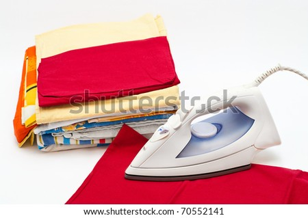 Flat electric iron and clothes on white background