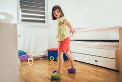 Flat feet correction exercise. Girl walking over spiked half balance massage balls