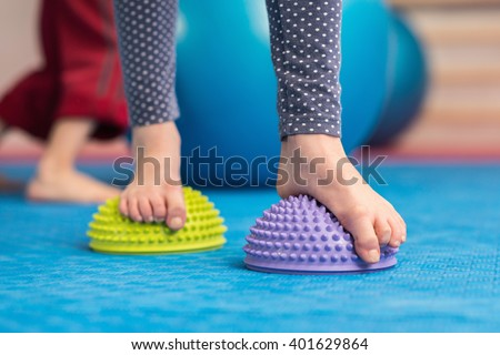 Flat feet correction exercise - Girl walking over spiked half balance massage balls