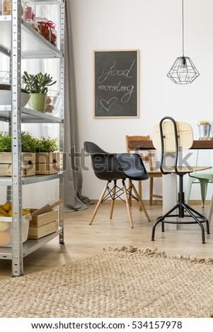 Flat in industrial style with table, chairs and simple regale