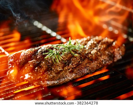 flat iron steak cooking on flaming grill with rosemary garnish