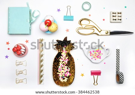 Flat lay. Accessories on the table, woman desk top. View top table, background mock up. Gold stationery,gold pineapple, mint box, colorful confettis, tea and strawberry.