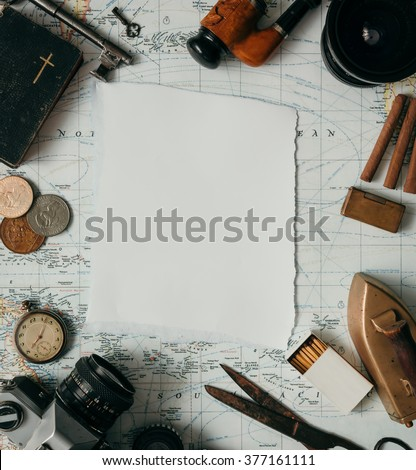 Flat lay adventure vintage gear for exploring or traveling on old map