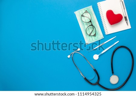 Photo of Flat lay aerial image of tools medical & Healthcare background concept.Table top view essential items for doctor using treat & care patient in hospital.Object on blue paper.Free space for design text.