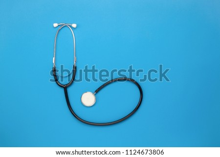 Flat lay aerial of tools medical & Healthcare insurance background concept.space for design.Table top view essential items for doctor using treat & care patient in hospital.Stethoscope on blue paper.