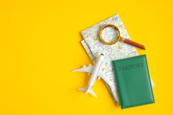 Flat lay airplane model, passport, map and magnifying glass on yellow background. Top view with copy space. Summer holiday vacation banner. Travel destination research concept