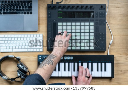 Flat lay and high angle above top view of tattoo hands of creativity disc jockey. Man using controller and mini piano keyboard for making music in black modern and sound studio with style interior