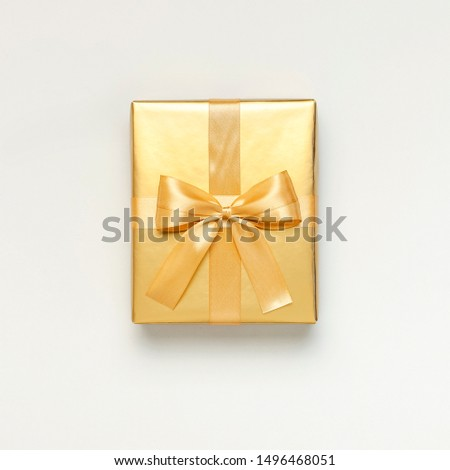 Flat lay Autumn holiday concept. Golden gift or present box with ribbon on light gray background top view copy space. Surprise, congratulation, birthday, greeting card