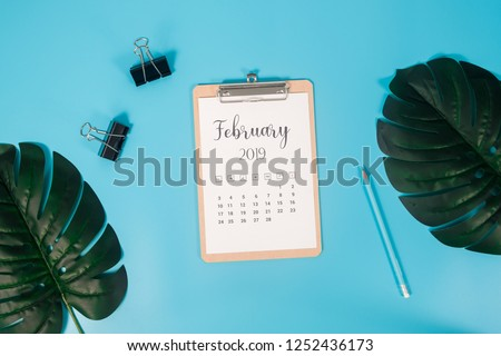 Flat lay calendar with clipboard, palm leaves and pencil on blue background. February 2019. top view.