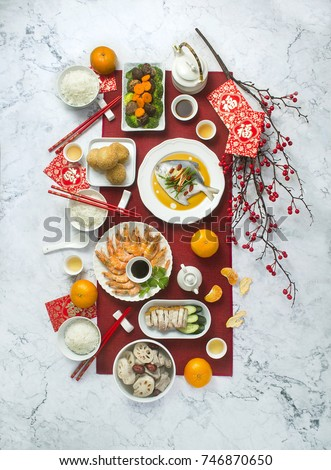 Flat lay Chinese new year reunion dinner food and drink still life. Marble table top. Text appear in image