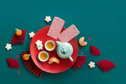 Flat lay Chinese new year tea set and snack on green background still life.