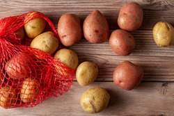 Flat lay  close up image featuring a red mesh potato sack with pink and yellow raw organic potatoes on wooden background. A versatile still life food image with randomly scattered potatoes.