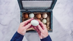 Flat lay. Colorful farm fresh eggs in vintage egg crate.