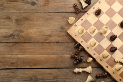 Flat lay composition of chess on wooden table, space for text. Board game