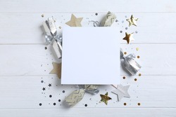 Flat lay composition of Christmas crackers, shiny confetti and blank paper on white wooden background. Space for text