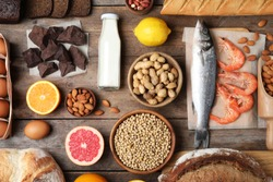 Flat lay composition of different products on wooden table. Food allergy concept