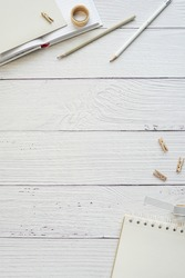 Flat lay composition on white wood background with notebook, pencils, work desk, vertical image for social media post, copy space.
