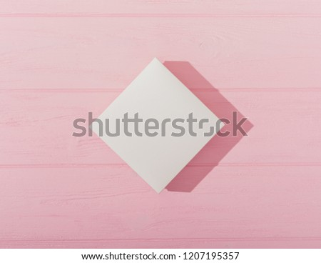 Flat lay composition rhombus blank gift. Top view empty white box casting shadow on pink wooden table. #1207195357