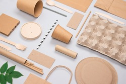 Flat lay composition, set of eco-friendly tableware and kraft paper food packaging on light gray background. Street food paper packaging - cups, plates, straws, containers and paper bags. Mockup