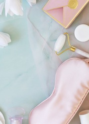 Flat lay composition with a sleep mask, perfume, cosmetic jars, massage roller, gift box and blooming magnolias on light blue marble background. Good morning, relax and skin care concept. Spring mood
