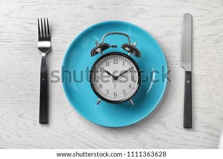 Flat lay composition with alarm clock, plate and utensils on light background #1111363628